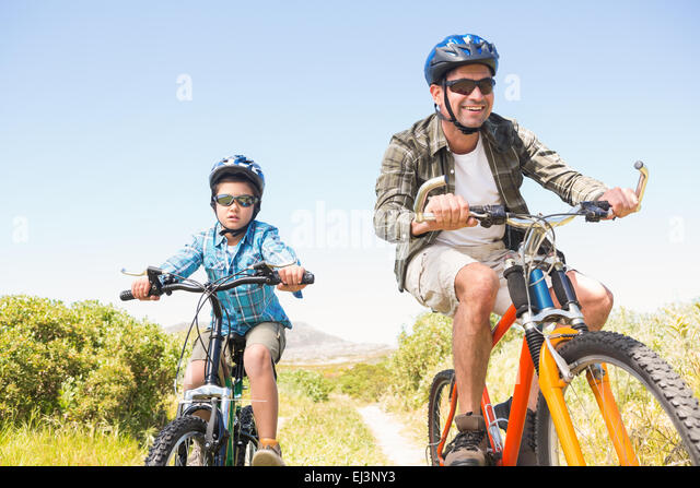 Father and son biking through mountains - Stock-Bilder