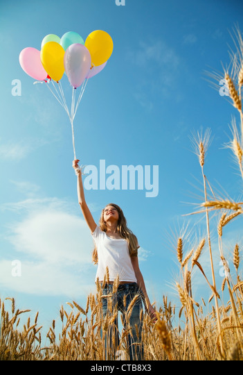 Teen girl at a wheat field with colorful balloons - Stock Image