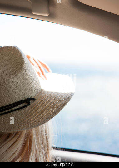 Back View of Woman Looking at the Ocean from Inside Car - Stock Image
