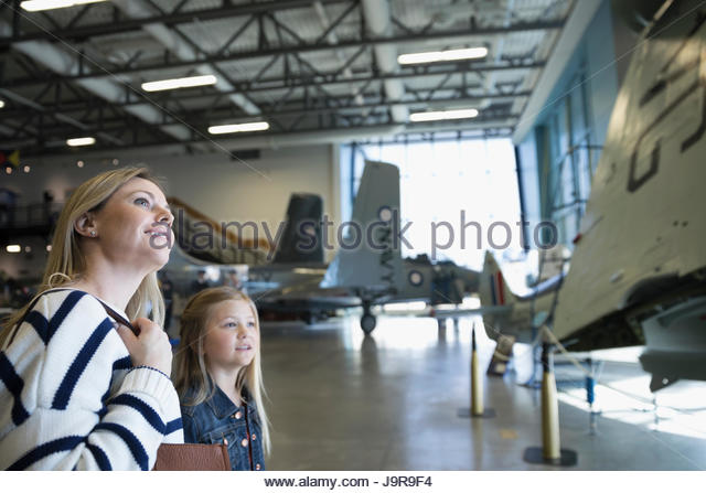 Curious mother and daughter looking up at airplane in war museum hangar - Stock-Bilder