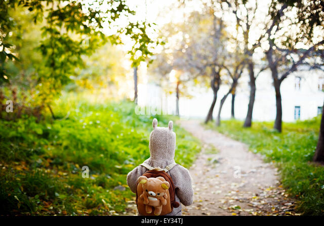 Cute Little Kid in Funny Jacket with Animal Ears on Hood and Teddy Bear Backpack Travelling in the Park. View from - Stock Image