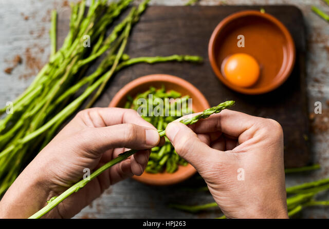 young man chopping wild asparagus with his hands and some earthenware bowls with chopped asparagus and a cracked - Stock Image