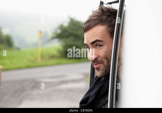 portrait of young man looking out of car window - Stock Image