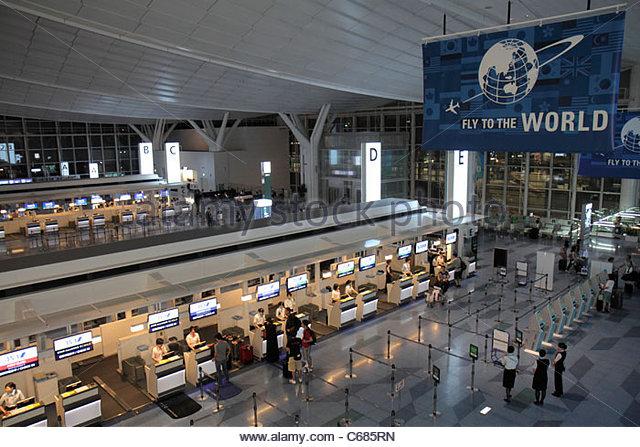 Japan Tokyo Haneda Airport kanji hiragana katakana characters symbols Japanese English Asian man woman check-in - Stock Image