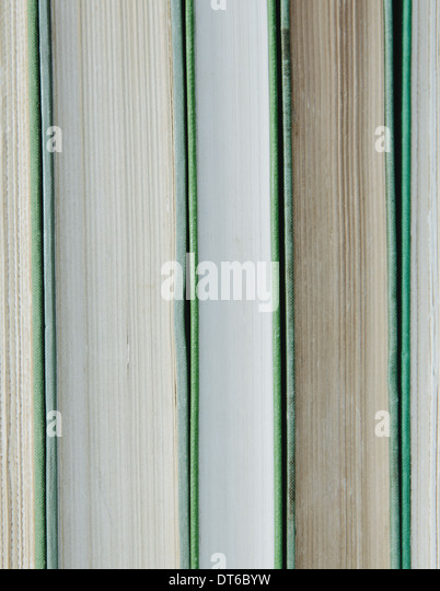 Books in a row, with green hard covers, and white and beige paper edges. - Stock Image