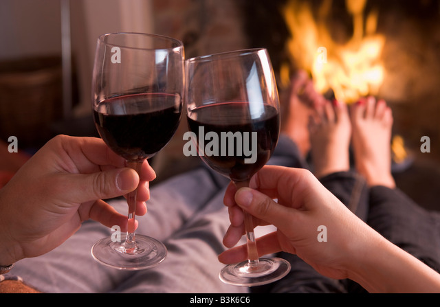 Feet warming at fireplace with hands holding wine - Stock Image