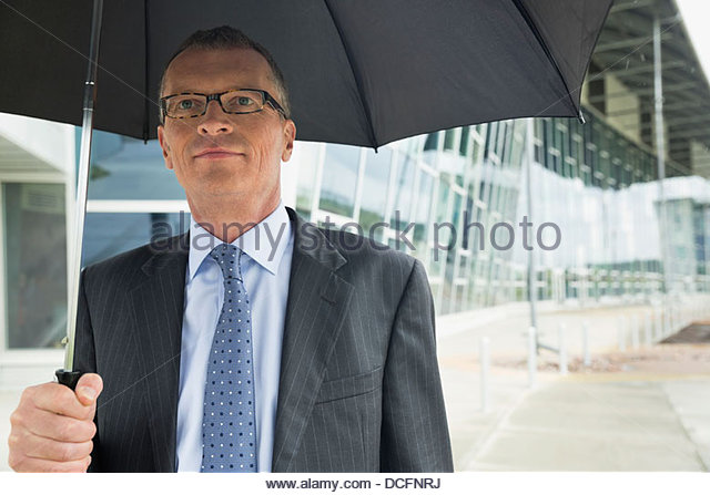 Confident businessman holding umbrella outside office building - Stock Image