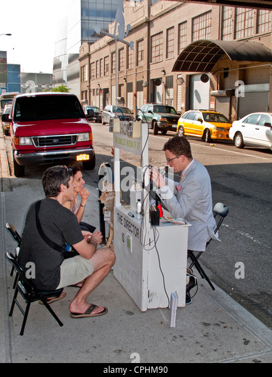 Passersby stop at the portable 'Homeless Museum of Art' on a sidewalk the lower west side of Manhattan, - Stock Image