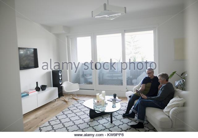 Senior couple using digital tablet on living room sofa - Stock Image