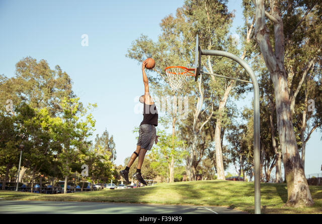 Man shooting basketball  hoops in the park at sunset - Stock Image
