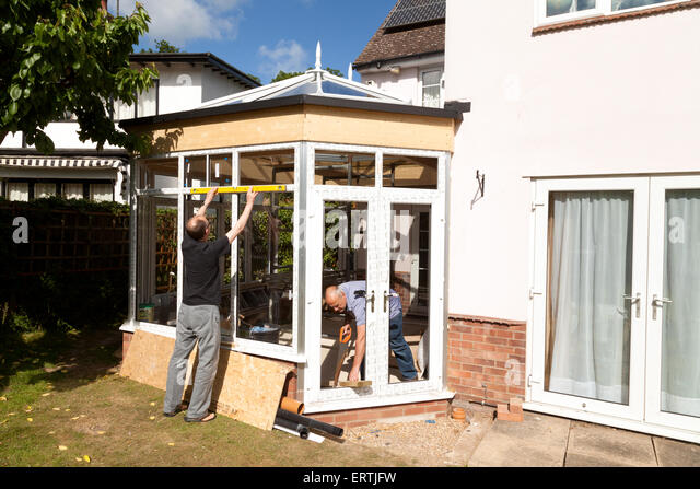 Builders at work building a conservatory as part of a house extension, UK - Stock Image