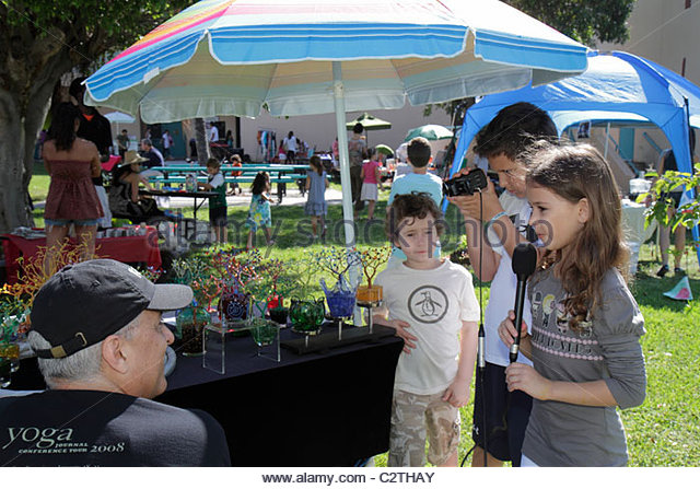 Miami Beach Florida South Pointe Elementary School PTA Green Market Fundraiser booth vendor boy girl student microphone - Stock Image