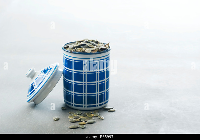 Pumpkin seeds in canister, overflowing - Stock Image