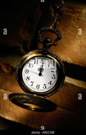Antique brass pocket watch on a brick wall - Stock Image