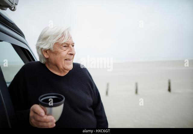 Happy senior man drinking coffee at car on winter beach - Stock Image