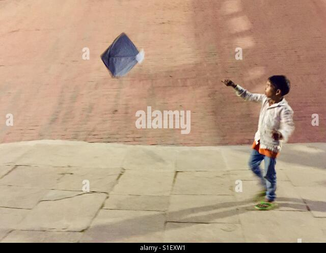 A young boy flies his kite at the bank of the river Ganges in Varanasi, India - Stock-Bilder