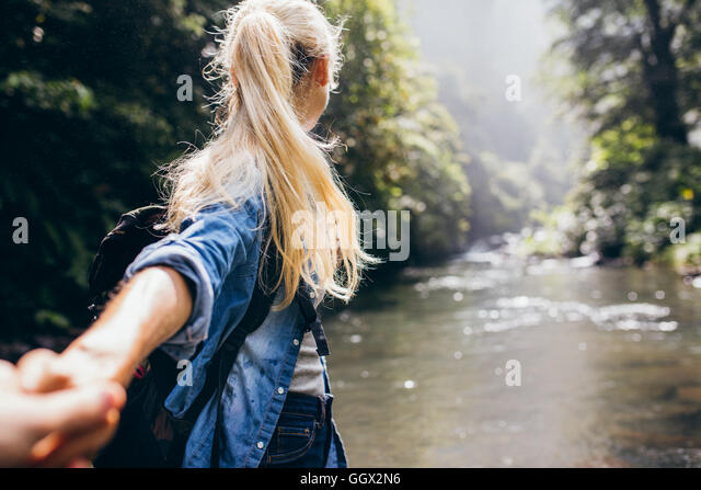 Young woman leading her boyfriend on the forest hike. Point of view shot of couple crossing the creek holding hands. - Stock Image
