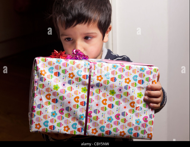 Boy holding a present - Stock Image