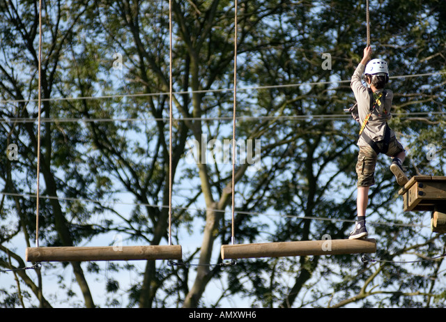 PICTURE CREDIT DOUG BLANE Boy crossing a log bridge at the Aerial Extreme Willen Lake Milton Keynes City of Milton - Stock Image