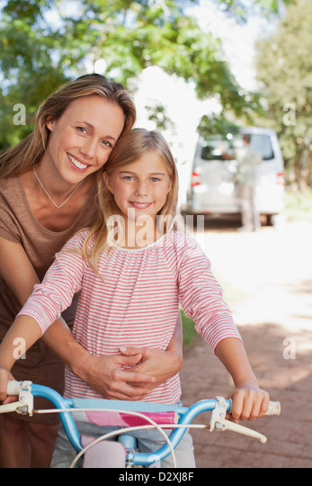 Portrait of smiling mother hugging daughter on bicycle - Stock Image
