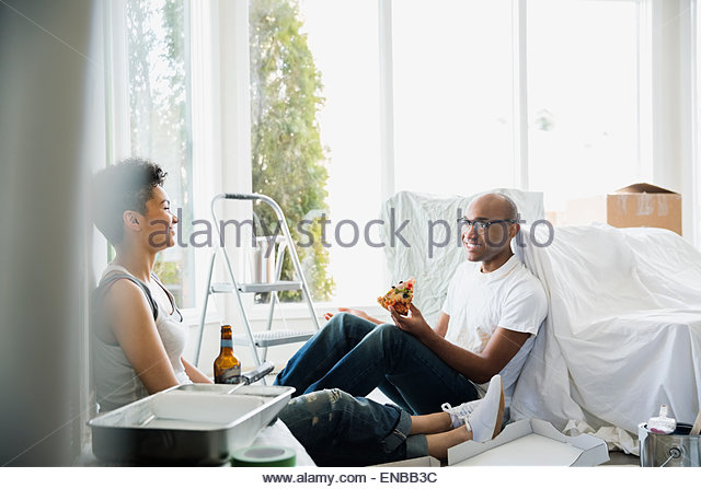 Couple taking a break from painting eating pizza - Stock Image