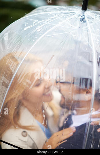 Portrait of affectionate couple under umbrella looking at one another - Stock-Bilder