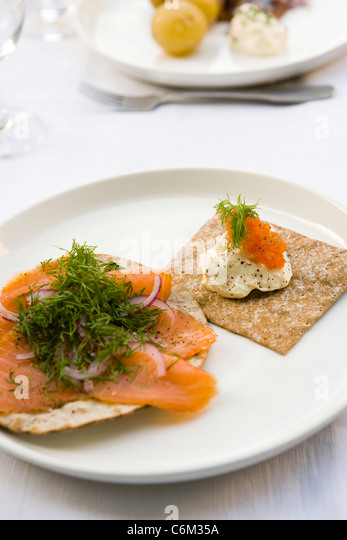 Crisp bread topped with smoked salmon and fresh dill, sour cream and salmon roe - Stock-Bilder