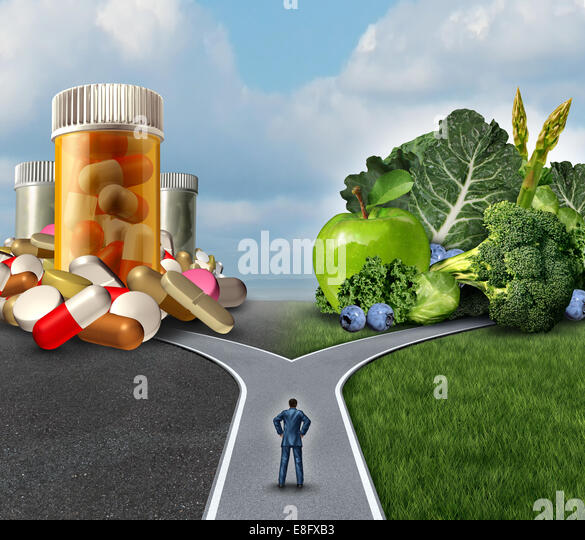 Medication decision concept and natural remedy nutrition choices dilemma between healthy fresh fruit and vegetables - Stock Image