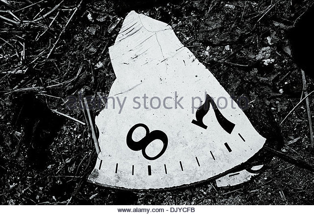 A fragment of a clock face numbers '8' and '7' lies abandoned in the edgelands surrounding the South - Stock Image