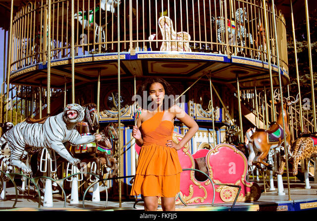 cool real teenage girl with candy near carousels at amusement park walking, having fun - Stock Image