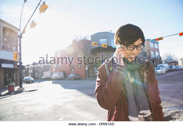 Young man answering smart phone outdoors - Stock-Bilder