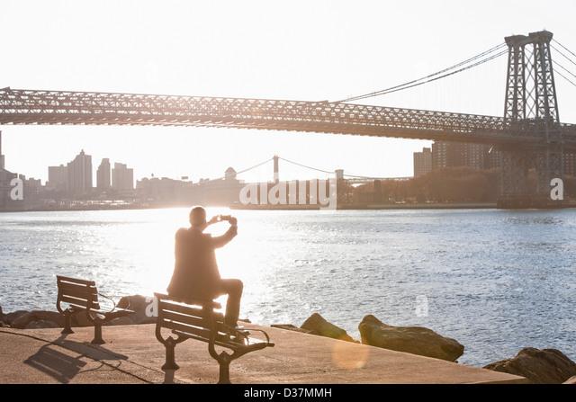 Man taking pictures of urban bridge - Stock-Bilder