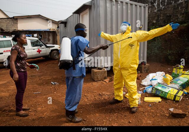 An ambulance driver in protective clothing is disinfected with chlorine after returning from transporting a Ebola - Stock Image
