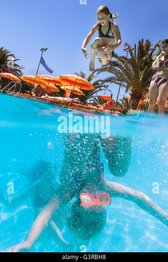 Italy, Sardinia, Alghero, Mother watching children (14-15, 16-17) diving into swimming pool - Stock Image