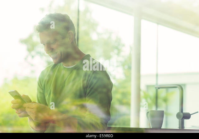 Man using cell phone viewed through window - Stock Image