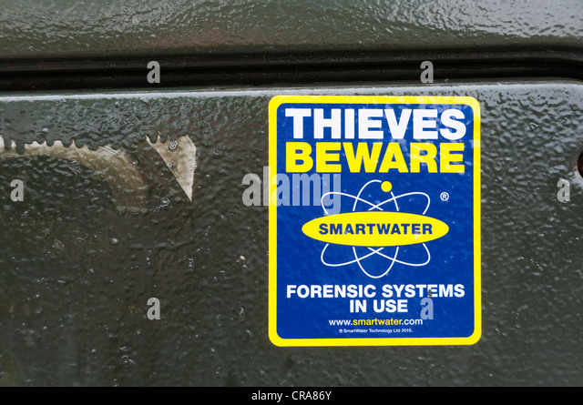 Thieves Beware Smartwater Forensic Systems In Use warning sticker on a telephone street cabinet. - Stock Image