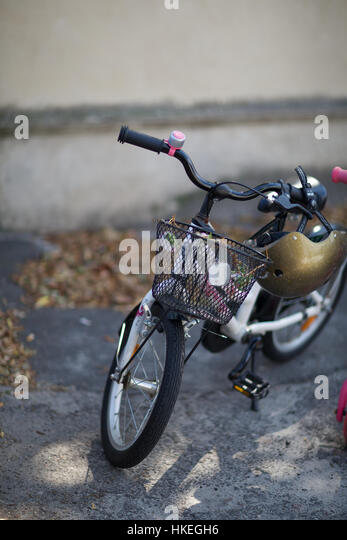 cycle parked in front of a wall. bicycle, helmet, basket, wheel. - Stock-Bilder