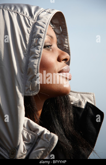 Woman wearing warm hooded jacket - Stock Image