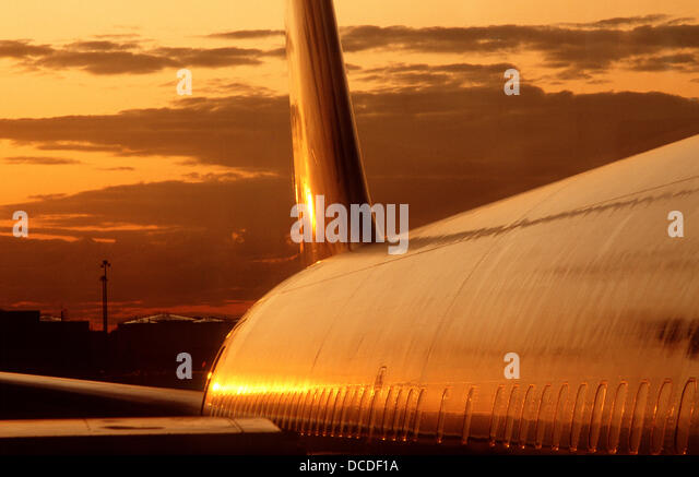 Fuselage of Boeing 767 aircraft reflecting sunset sky - Stock Image