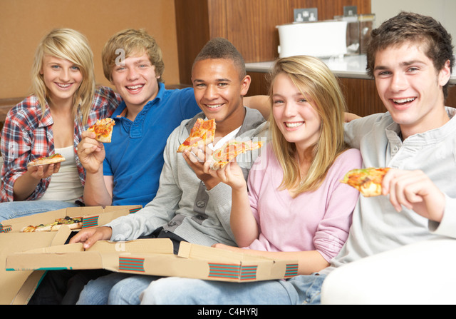 Group Of Teenage Friends Sitting On Sofa At Home Eating Pizza - Stock Image