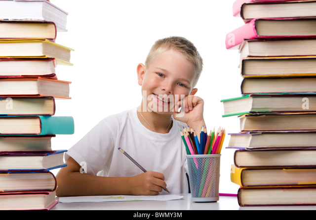 Portrait of cute youngster sitting among stacks of literature and smiling at camera while drawing - Stock Image