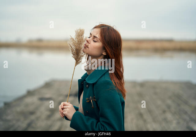 Caucasian woman standing on dock smelling stalk of grass - Stock Image