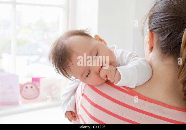 Baby girl sleeping on mother's shoulder - Stock-Bilder