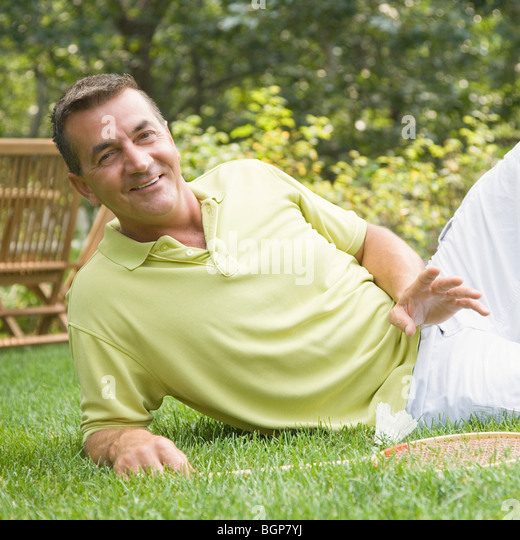 Portrait of a mature man reclining on grass with a badminton racket and a shuttlecock - Stock Image