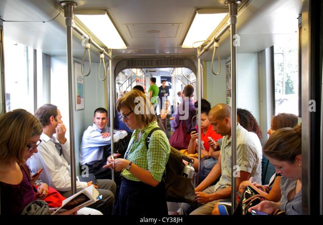 Boston Massachusetts MBTA T Green Line subway inbound train riders man woman checking smartphone reading - Stock Image