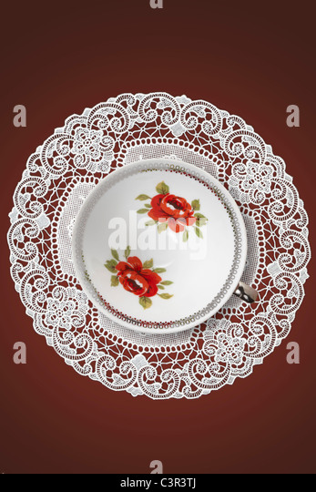 Coffee cup on rubber place mat against brown background - Stock Image