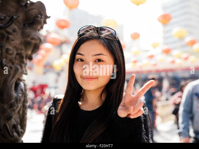 Portrait of young woman with long hair and sunglasses on head doing peace sign, looking at camera - Stock-Bilder