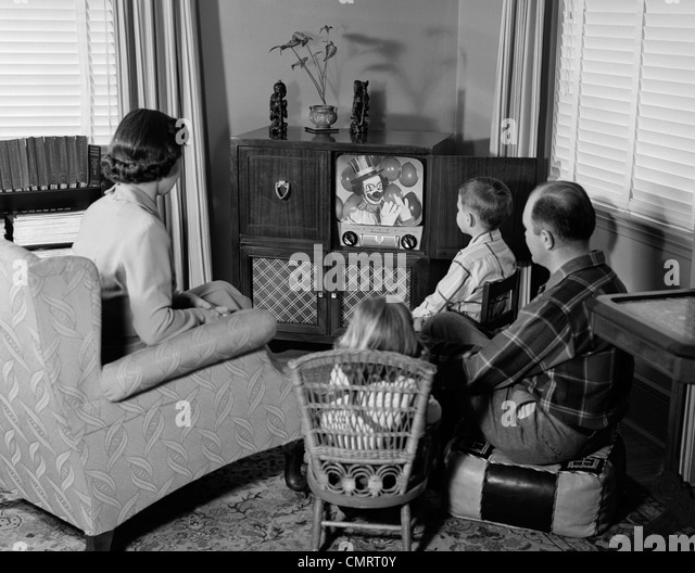 1950s BACK VIEW OF FAMILY OF 4 GATHERED AROUND TV SET WATCHING CLOWN WITH BALLOONS - Stock Image