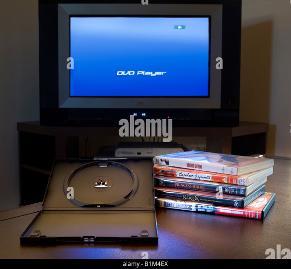 A pile of DVD films ready for a movie marathon, with a television and DVD player in the background - Stock Image
