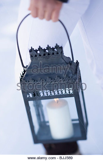 Person carrying Christmassy lantern out of doors - Stock Image